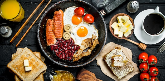 Traditional english breakfast with fried eggs, sausages and aromatic coffee on rustic table.