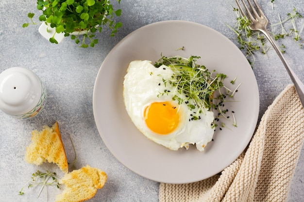 회색 콘크리트 이전 테이블에 회색 세라믹 접시에 arugula microgreen과 달걀 프라이와 전통적인 영국식 아침 식사. 평면도.