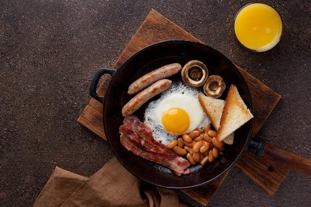 Традиционный английский завтрак с жареными сосисками, яичницей, беконом, тостами с грибами и фасолью