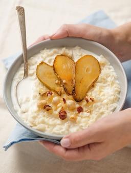 Традиционный английский завтрак. женщина держит миску овсяных хлопьев или каши с орехами и грушами. крупным планом выстрел. мягкий фокус.