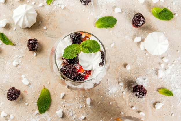 Traditional english dessert. eton mess - whipped cream, meringue, fresh blackberries, sauce and caramel. in serving glasses on a light stone table. copy space top view