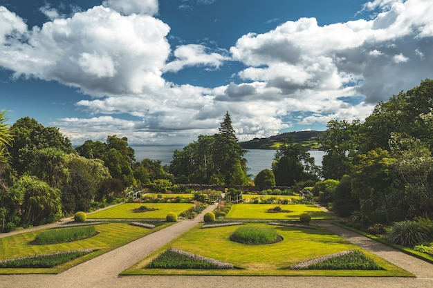 Traditional english park lawns surrounded by the trees. northern ireland. stylish landscape design. blue cloudy sky, calm water surface background. cozy walking paths. ideal place for the rest.