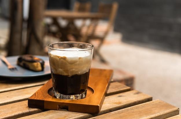 나무 테이블에 흰색 거품 크림 컵과 전통적인 에스프레소 커피