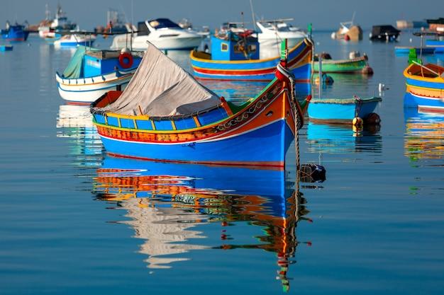マルタ、マルサシュロックの地中海漁村の港にある伝統的な目をしたカラフルなボートluzzu