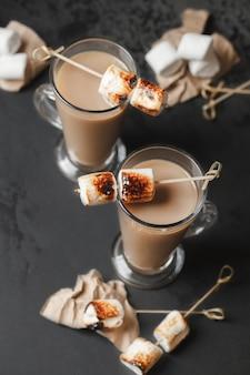 伝統的な秋と冬のカクテル、アルコール。キャンプファイヤーホットチョコレートカクテルとローストマシュマロ。ココアラテマシュマロ