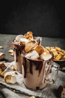 Традиционные осенние и зимние коктейли, алкоголь. коктейль из горячего шоколада у костра с добавлением соленых крекеров и жареного зефира, в двух кружках, на черном каменном столе, copyspace