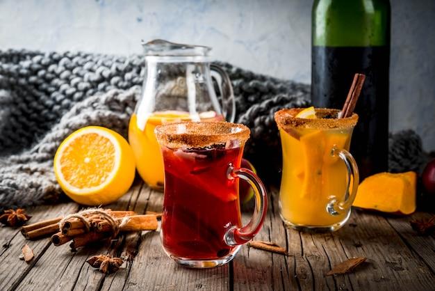 Традиционные осенние и зимние напитки и коктейли. белые и красные осенние острые пряные сангрии с анисом, корицей, яблоком, апельсином, вином. в стеклянных кружках, старый деревенский деревянный столик. выборочный фокус копией пространства