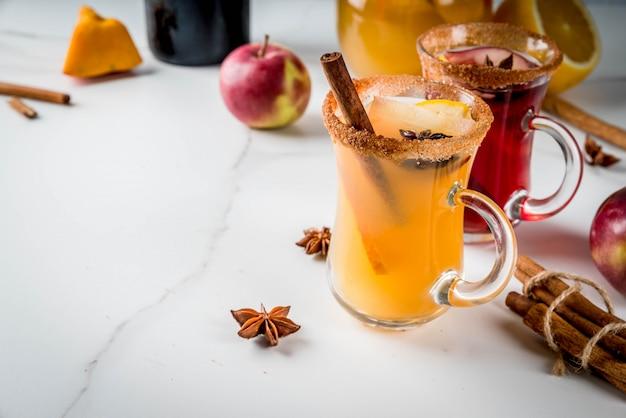 Традиционные осенние и зимние напитки и коктейли. белые и красные осенние острые пряные сангрии с анисом, корицей, яблоком, апельсином, вином. в стеклянных кружках, белый мраморный стол. выборочный фокус копией пространства