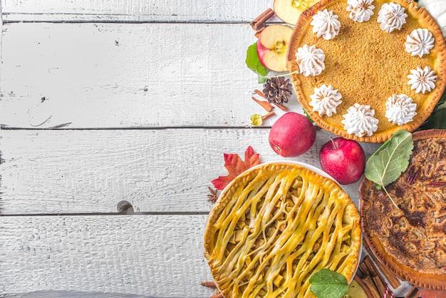 伝統的な秋のベーキング。アメリカとヨーロッパの伝統的な秋冬のケーキ-カボチャ、ピーカンナッツ、リンゴ