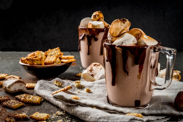 Traditional fall and winter cocktails, alcohol. campfire hot chocolate eggnog cocktail with salted crackers and roasted marshmallow, in two mugs, on black stone table,
