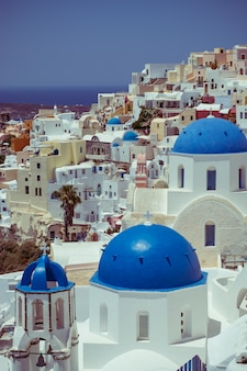 Traditional and famous houses and churches with blue domes over the caldera, aegean sea