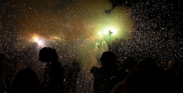 Традиционный праздник каталонии люди танцуют под огнем и под звуки петард.