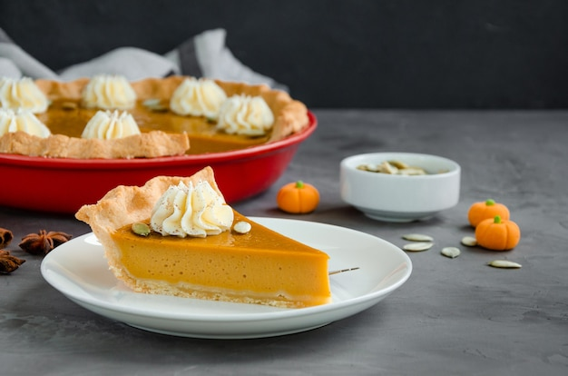 Traditional festive pumpkin pie with spices whipped cream and seeds dessert for thanksgiving