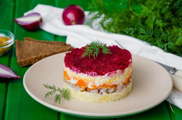 Традиционная праздничная русская салатная сельдь под шубой на тарелке. салат с соленой рыбой и вареными овощами.