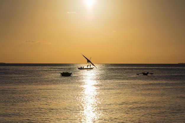 Традиционная рыбацкая лодка доу во время заката в индийском океане на острове занзибар, танзания, восточная африка