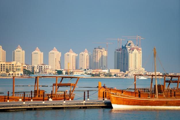Традиционная рыбацкая лодка в стыковке с городом на фоне длинной причала со спокойной голубой водой