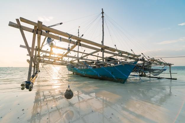 Традиционная рыбацкая лодка на тропическом пляже карибского моря. индонезия архипелаг молуккас, острова кей. рыболовство индонезийских культур.