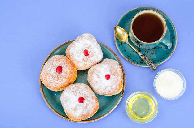 Traditional food doughnuts with icing sugar and jam. jewish holiday hanukkah.