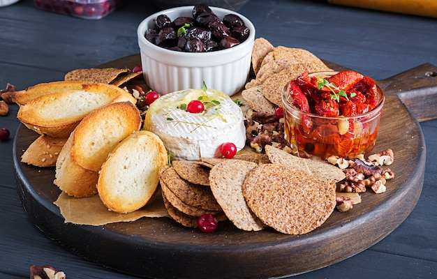 Traditional french baked camembert cheese with thyme and toast, walnuts, olives, sun dried tomatoes, and flax chips.