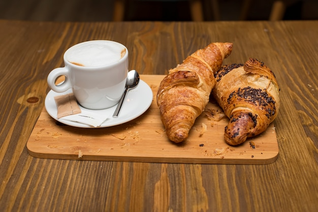 Traditional french breakfast with cups of hot coffee and fresh tasty croissants placed on vintage table