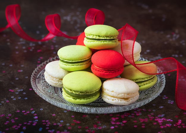 Traditional french colorful macarons in a glass plate on dark background with copy space.