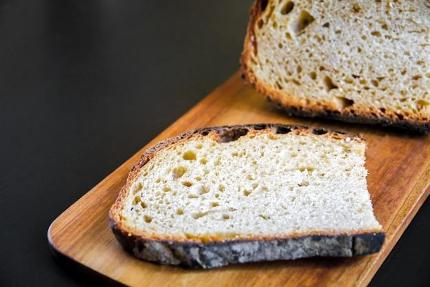 木製のまな板に伝統的なフランスの国のパンのスライス