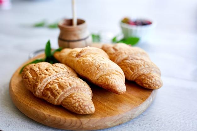 Традиционный французский круассан на фоне белого стола, вкусный завтрак с круассанами, свежая выпечка, вид сверху
