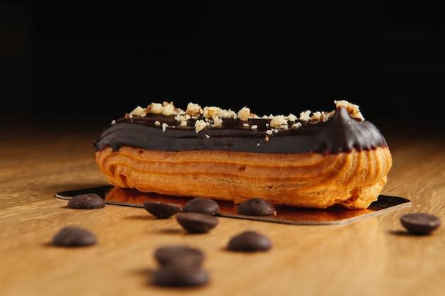 チョコレートと伝統的なフランスのエクレア。おいしいデザート。自家製ケーキエクレア。クリームがたっぷり入ったスウィートデザートペストリー。チョコレートのアイシング。