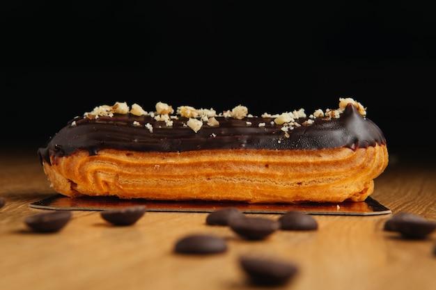 Традиционный французский эклер с шоколадом. вкусный десерт. домашние эклеры из торта. сладкое десертное тесто с кремовой начинкой. шоколадная глазурь.
