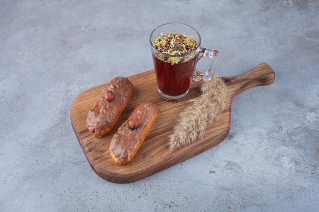Eclairs francesi tradizionali con cioccolato e una tazza di tè di vetro.