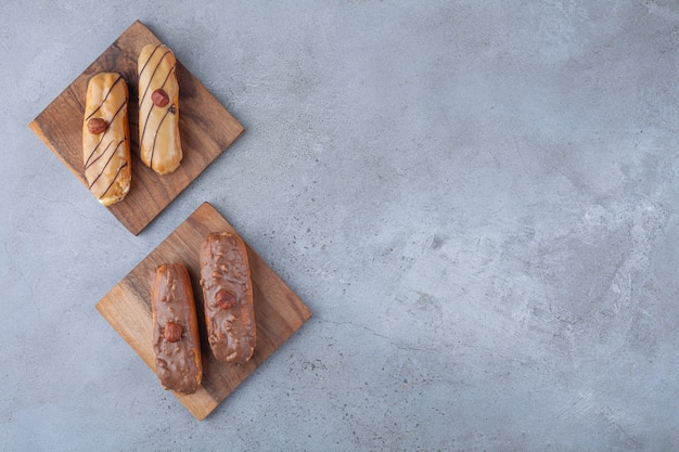 Traditional french eclairs with chocolate placed on wooden board .