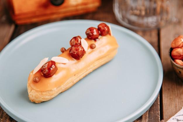 Традиционные французские эклеры со сливками. эклеры, украшенные шоколадом и ягодами на тарелке.