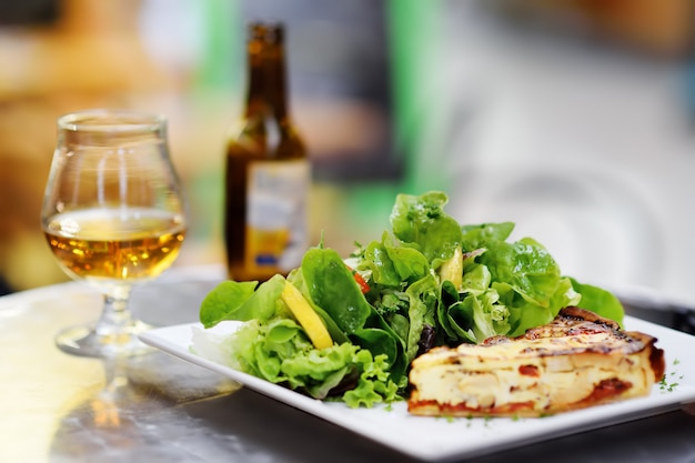 Traditional french food: quiche lorraine and fresh salad leaves with glass of beer on background