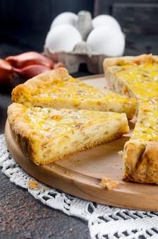 전통적인 프랑스 수제 양파 파이 또는 치즈. 어두운 테이블에 라운드 보드에 치즈와 양파 파이를 엽니 다.