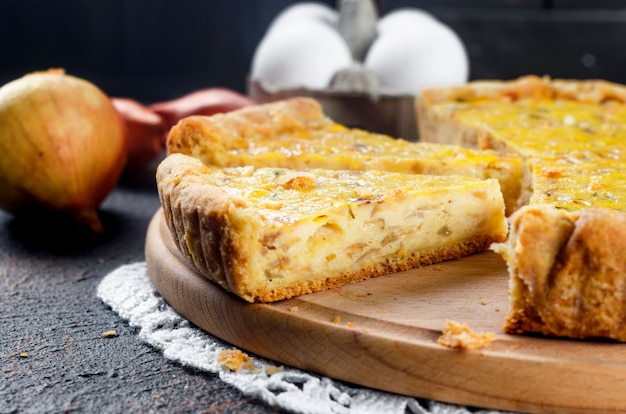 Traditional french homemade onion pie or quiche. open pie with cheese and onion on round board
