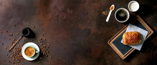 커피와 우유의 종이 컵, 지팡이 설탕의 재활용 된 나무 숟가락, 어두운 질감 테이블 위에 터키어 커피와 슬레이트 나무 보드에 전통적인 프랑스 퍼프 페이스 트리 초콜릿 롤빵. 플랫 레이, 공간