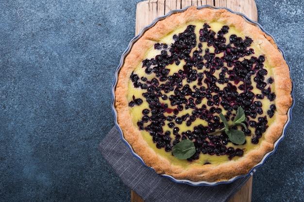青いコンクリートの表面にブルーベリーと伝統的なフランスの甘いフルーツデザートクラフティ。コピースペースを持つ健康的なグルテンフリー食品のコンセプト。