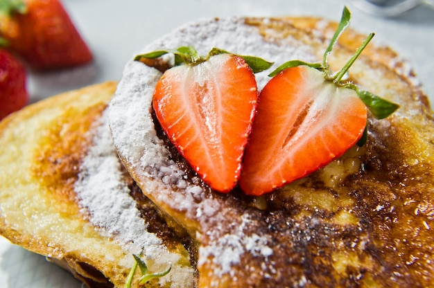 Traditional french toast with strawberries for breakfast.