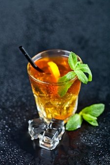 Traditional fresh iced tea with lemon, mint leaves and ice cubes in glass.