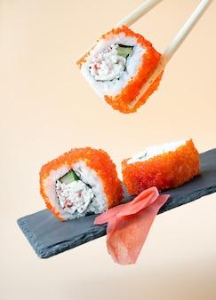 Традиционные свежие японские суши-роллы и имбирь. левитация
