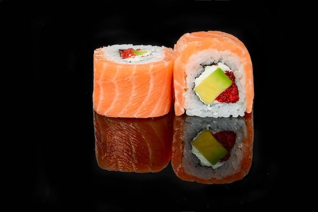 Traditional fresh japanese sushi rolls on a black background
