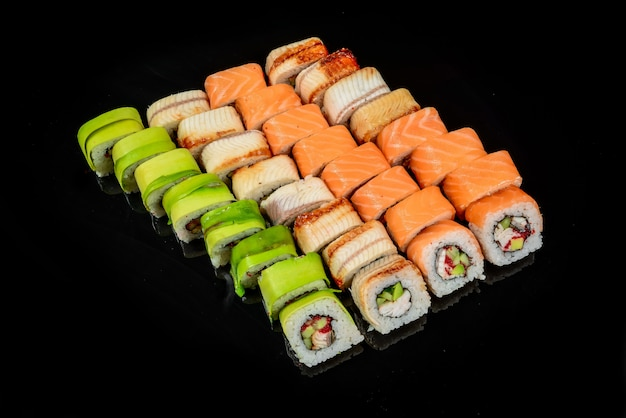 Traditional fresh japanese sushi rolls on a black background