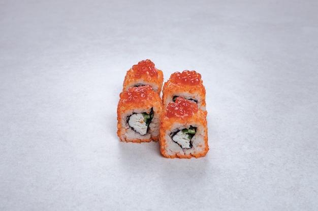 Rotoli di sushi freschi tradizionali sulla superficie bianca.