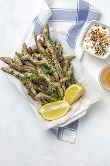 Традиционные жареные анчоусы с лимоном и петрушкой. концепция морепродуктов