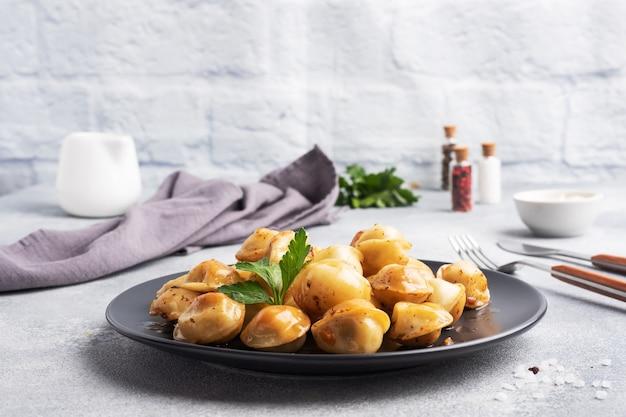 전통적인 튀긴 pelmeni, 라비올리, 검은 접시, 러시아 부엌에 고기로 가득한 만두. 회색 콘크리트 테이블, 복사 공간.