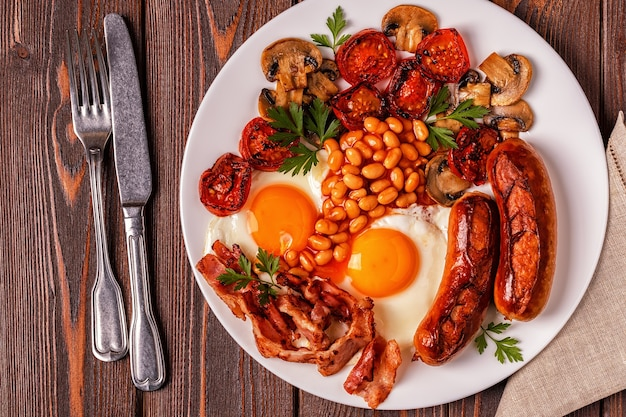 튀긴 계란, 소시지, 콩, 버섯, 구운 토마토, 베이컨 나무 배경에 전통적인 영국식 아침 식사