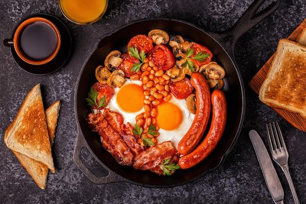 Традиционный полный английский завтрак с яичницей, сосисками, фасолью, грибами, жареными помидорами и беконом.
