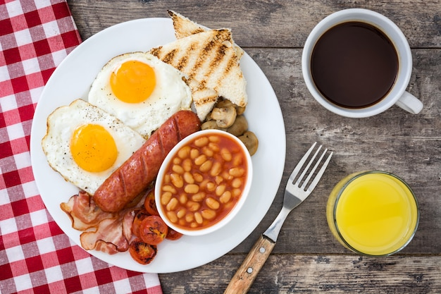 Traditional full english breakfast with fried eggs, sausages, beans, mushrooms, grilled tomatoes and bacon on wooden surface top view