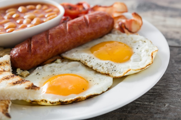 Traditional full english breakfast with fried eggs, sausages, beans, mushrooms, grilled tomatoes and bacon on wooden surface