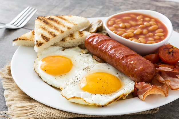 Traditional full english breakfast with fried eggs, sausages, beans, mushrooms, grilled tomatoes and bacon on wooden surface.